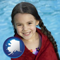 alaska map icon and a little girl wrapped in a dark red towel, in front of a swimming pool