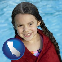 california map icon and a little girl wrapped in a dark red towel, in front of a swimming pool