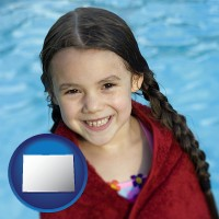 colorado map icon and a little girl wrapped in a dark red towel, in front of a swimming pool