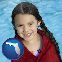 florida map icon and a little girl wrapped in a dark red towel, in front of a swimming pool