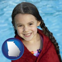 georgia map icon and a little girl wrapped in a dark red towel, in front of a swimming pool