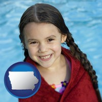 iowa map icon and a little girl wrapped in a dark red towel, in front of a swimming pool