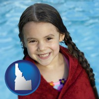 idaho map icon and a little girl wrapped in a dark red towel, in front of a swimming pool