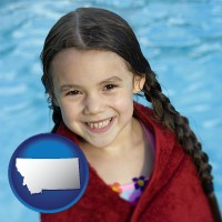 montana map icon and a little girl wrapped in a dark red towel, in front of a swimming pool