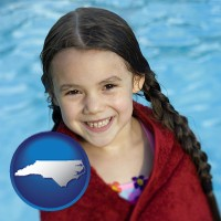 north-carolina map icon and a little girl wrapped in a dark red towel, in front of a swimming pool