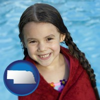 nebraska map icon and a little girl wrapped in a dark red towel, in front of a swimming pool