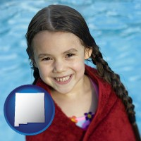 new-mexico map icon and a little girl wrapped in a dark red towel, in front of a swimming pool