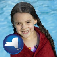 new-york map icon and a little girl wrapped in a dark red towel, in front of a swimming pool