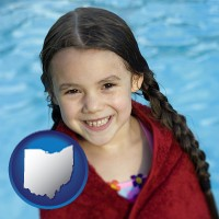 ohio map icon and a little girl wrapped in a dark red towel, in front of a swimming pool