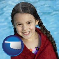 oklahoma map icon and a little girl wrapped in a dark red towel, in front of a swimming pool