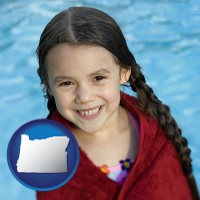 oregon map icon and a little girl wrapped in a dark red towel, in front of a swimming pool