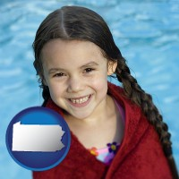 pennsylvania map icon and a little girl wrapped in a dark red towel, in front of a swimming pool