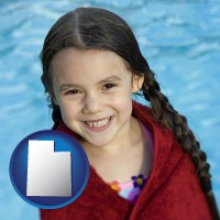 utah map icon and a little girl wrapped in a dark red towel, in front of a swimming pool