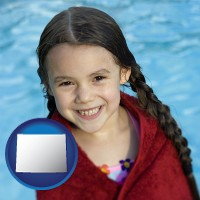 wyoming map icon and a little girl wrapped in a dark red towel, in front of a swimming pool