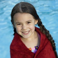 a little girl wrapped in a dark red towel, in front of a swimming pool